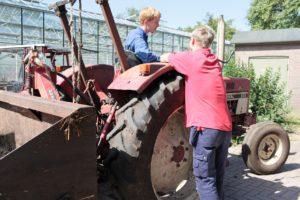 Menschen und Traktor in Urtica